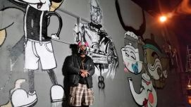 MR. BLACKBRAIN IN FRONT OF MURAL
